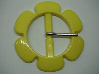 Fibbia in plastica a forma di fiore giallo.