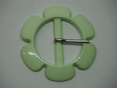 Fibbia in plastica a forma di fiore verdino.